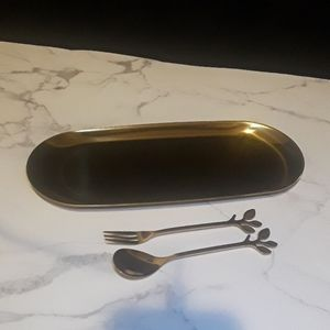 Gold tray with tea spoon and fruit fork.